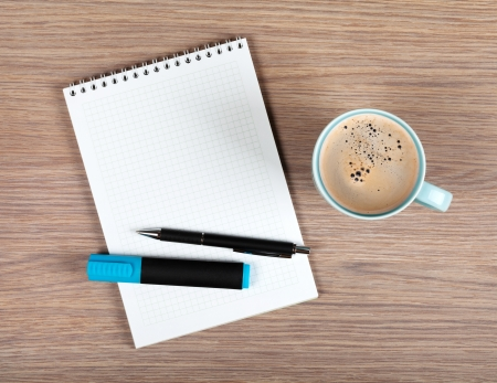 Blank notepad and coffee cup on office wooden table Reklamní fotografie