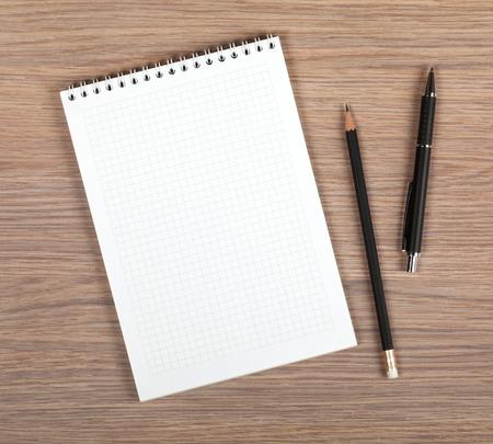 ペンと鉛筆を木製のオフィスのテーブル上で空白のメモ帳