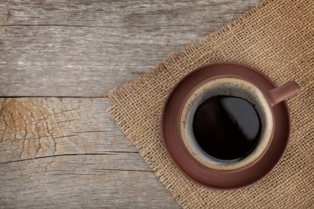 Coffee cup on wooden table texture. View from above photo