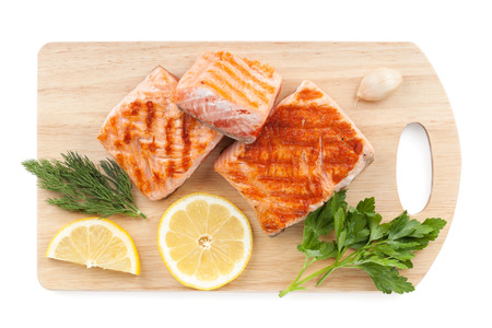 cooked fish: Grilled salmon with lemon slices and parsley on cutting board. Isolated on white background
