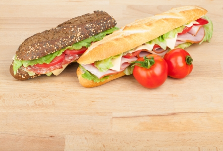 Fresh sandwiches with meat and vegetables and tomatoes on wood table photo