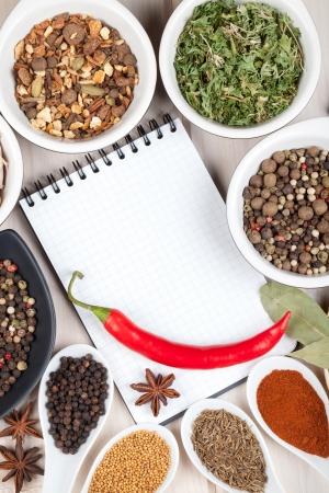 cilantro: Hierbas y especias en la mesa de madera con la libreta en blanco para copyspace Foto de archivo