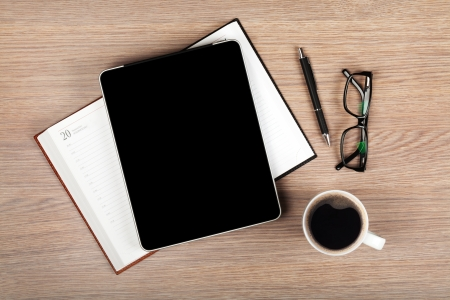 note pad and pen: Tablet with blank screen and coffee cup on office wooden table