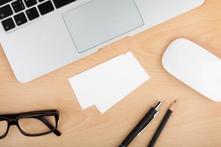 papeleria: Tarjetas en blanco con los suministros en la oficina de mesa de madera