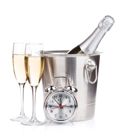 Champagne bottle in bucket, two glasses and alarm clock. Isolated on white background photo