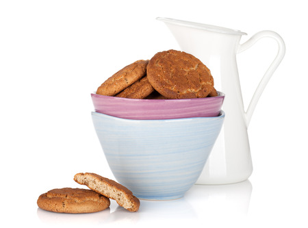 Cookies bowl and milk jug. Isolated on white photo