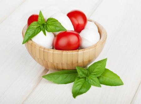 チェリー トマトと白の木のテーブルにバジルとモッツァレラチーズ