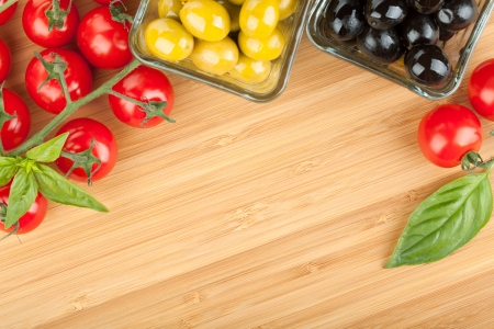 chopping: Olives, tomatoes and basil on cutting board with copyspace