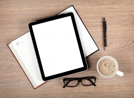 Tablet with blank white screen and coffee cup on office wooden table photo