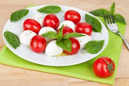 plato de ensalada: Plato de ensalada Caprese en mesa de madera Foto de archivo