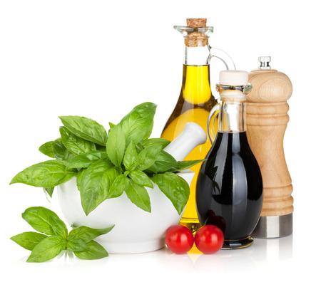 Olijfolie, azijn flessen met basilicum en tomaten. Geïsoleerd op witte achtergrond