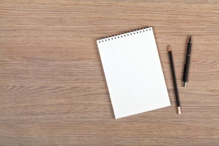 ペンと鉛筆木製のオフィスのテーブルを空白のメモ帳