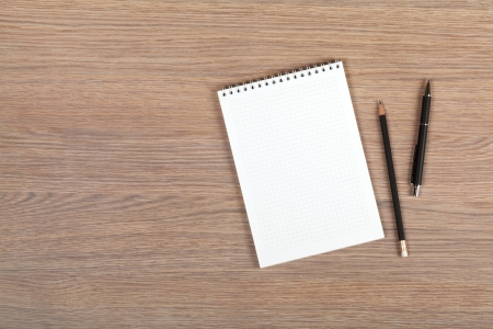 pads: Blank notepad with pen and pencil on office wooden table Stock Photo