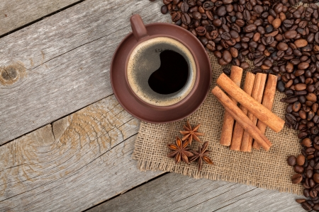 Coffee cup and spices on wooden table texture. View from above photo
