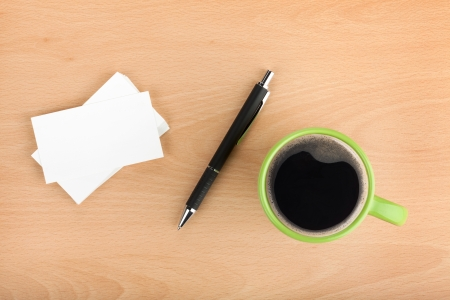 Blank business cards with pen and coffee cup on wooden office table photo