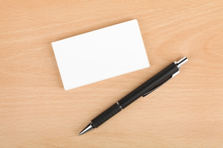 Blank business cards and pen on wooden office table photo