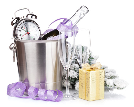 Christmas champagne with alarm clock in bucket and gift box. Isolated on white background photo