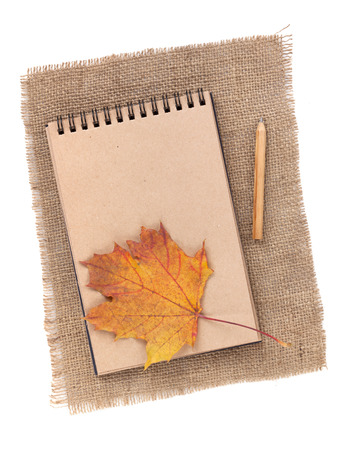 Brown paper notepad with pencil and autumn leaf over burlap. Isolated on white background photo