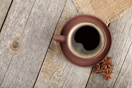 Coffee cup with anise on wooden table texture. View from above photo