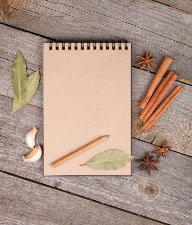 Blank notepad for copy space and herbs on wooden table photo