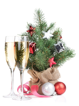 Small christmas tree with decor and two champagne glasses. Isolated on white background photo