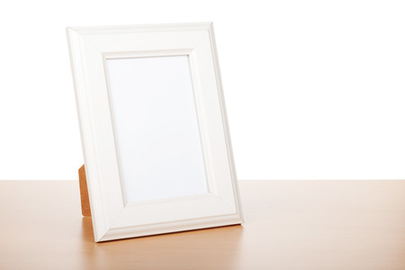 old photo: Photo frame on wood table. Isolated on white background Stock Photo