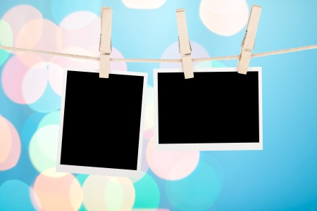 Blank photos hanging on clothesline over blue lights bokeh background photo