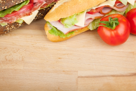 Fresh sandwiches with meat and vegetables and tomatoes. Closeup on wood table photo