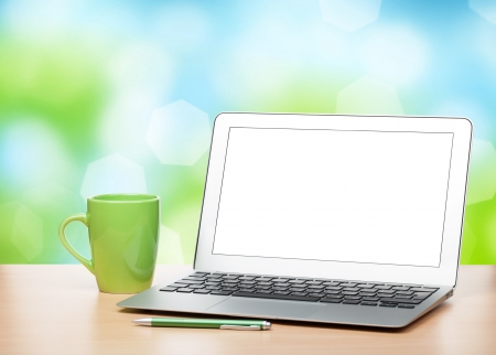 Laptop with blank screen and cup on table over sunny day bokeh background photo