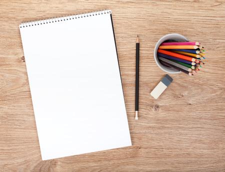 나무 테이블에 빈 종이와 다채로운 연필. 위에서보기