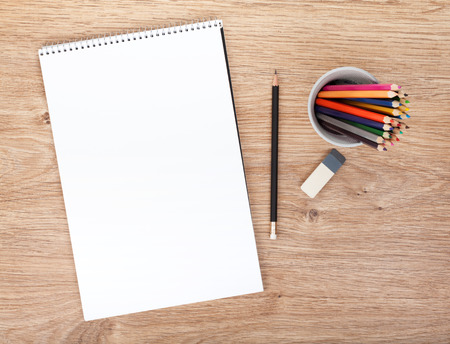 수첩: 나무 테이블에 빈 종이와 다채로운 연필. 위에서보기