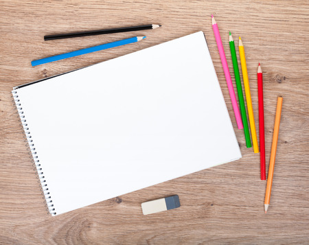 Blank paper and colorful pencils on the wooden table. View from above Stock Photo