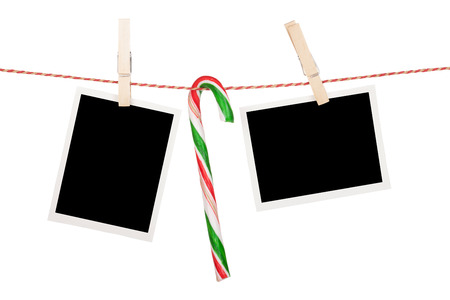 Blank photos and candy cane hanging on clothesline. Isolated on white background photo