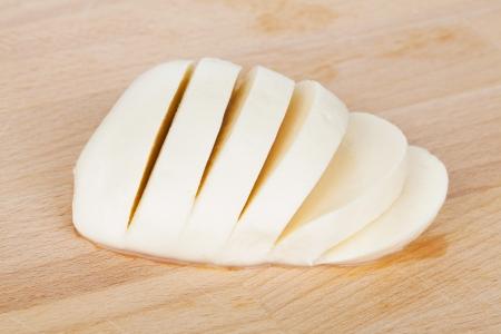 sliced cheese: Sliced mozzarella on wood table Stock Photo