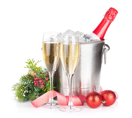 Champagne bottle in ice bucket, two glasses and christmas decor. Isolated on white background photo