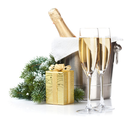 Champagne bottle in ice bucket, two glasses and christmas gift. Isolated on white background photo