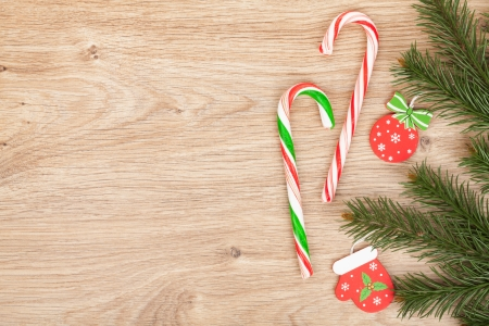 Christmas fir tree and candy cane on wooden board photo