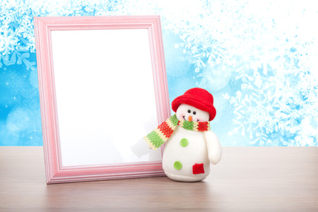 Blank photo frame and christmas snowman on wooden table over blue christmas background photo