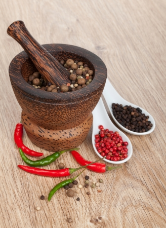 pepper grinder: Mortar and pestle with red hot chili pepper and peppercorn on wooden table