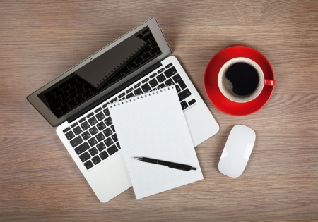 pad pen: Libreta en blanco sobre la computadora port�til y la taza de caf� en la mesa de madera de la oficina Foto de archivo