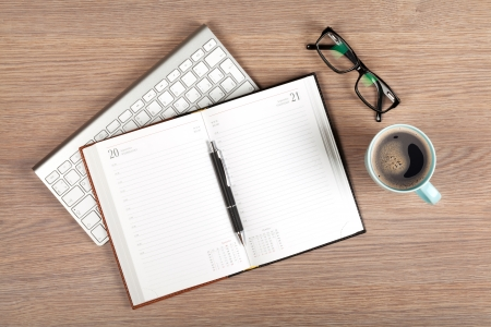 Blank notepad and coffee cup on office wooden table Stock Photo - 23845903