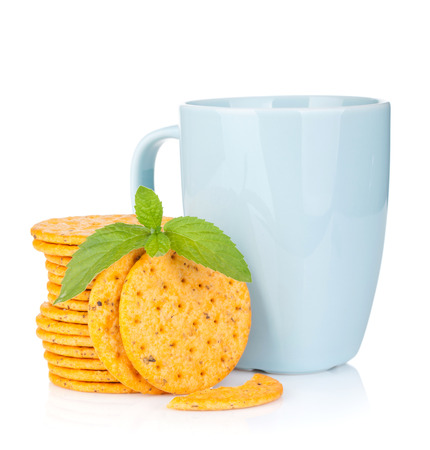 Stack of crackers with mint and cup of drink. Isolated on white background photo