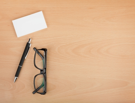 office table: Blank business cards with pen and glasses on wooden office table with copy space