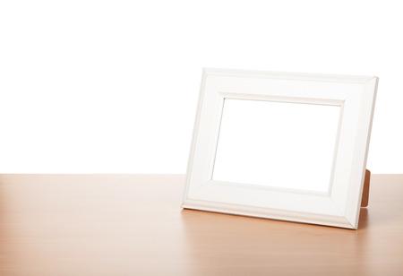 photo: Photo frame on wood table. Isolated on white background Stock Photo
