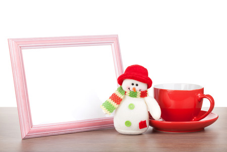 Blank photo frame, christmas snowman and coffee cup on wooden table. Isolated on white background photo