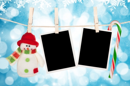 Blank photo frames and snowman hanging on the clothesline over blue christmas background photo