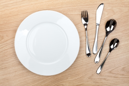 Empty white plate with silverware on wooden table. View from above photo