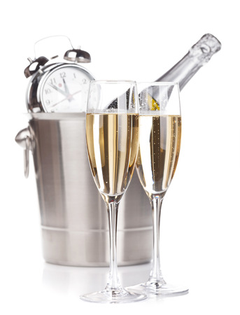 Two champagne glasses, bottle in bucket and alarm clock. Isolated on white  photo