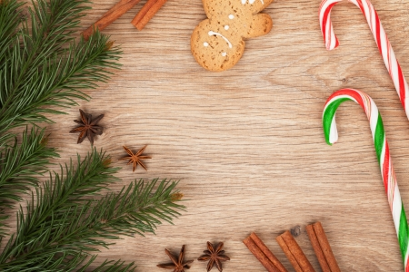 Christmas fir tree, gingerbread cookie and candy cane on wooden background photo