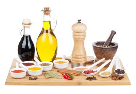 Various spices selection on cutting board. Isolated on white background photo